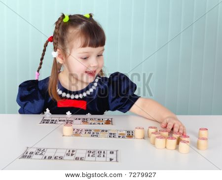 Child Playing With Bingo At The Table