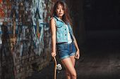 pic of skate board  - Beautiful Asian teen girl with skate board. Outdoors, urban lifestyle.