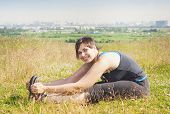 stock photo of hamstring  - Beautiful plus size woman stretching outdoor in summer - JPG