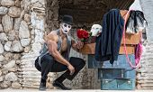 image of clown rose  - Handsome muscular cirque performer kneeling next to luggage