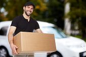 picture of moving van  - Smiling delivery man holding a paper box - JPG