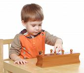 image of child development  - Little boy sitting at a table with educational toys - JPG