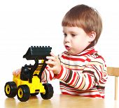 picture of child development  - little boy sitting at a table and playing in the machine - JPG