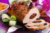 stock photo of prunes  - roasted pork loin stuffed with prune and spices on festive table - JPG