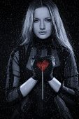 stock photo of gothic girl  - Cold gothic girl in corset with red sweet heart in her hands - JPG