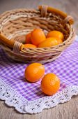 foto of kumquat  - Ripe fruit kumquat orange lying on a wooden surface against the background of a wicker basket - JPG
