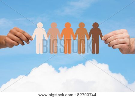 community, unity, people and support concept - couple hands holding paper chain multiracial people over blue sky and cloud background