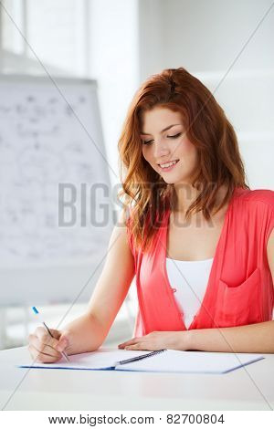 education and school concept - smiling student with textbook at school