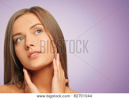 beauty, people and health concept - beautiful young woman touching her face and neck over violet background