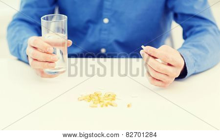 health, healthcare, medicine, medication, drugs, concept - close up of male hand holding pill and glass of water