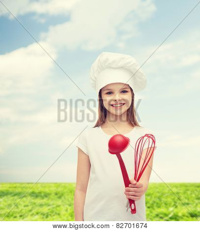 cooking and people concept - smiling little girl in cook hat with ladle and whisk