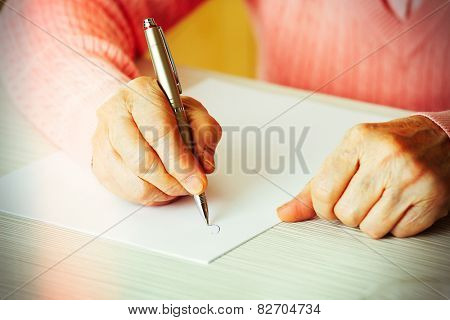 Hands of adult woman writing with pen, on table