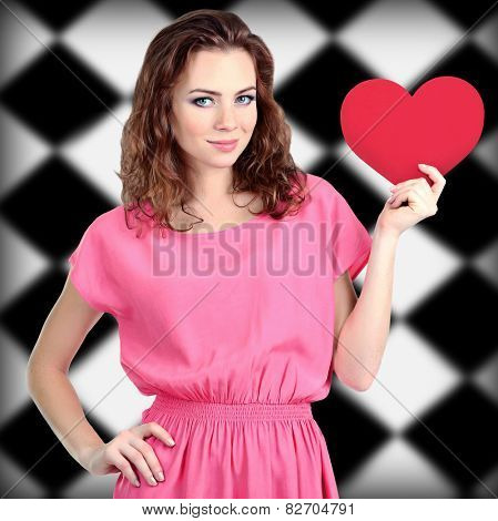 Beautiful young girl with heart in hands on checkered background