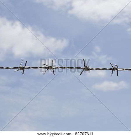 Barb Wire Fence With Blue Sky