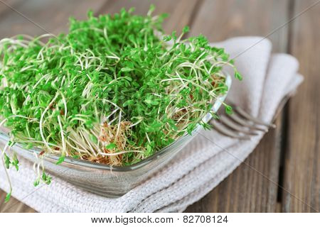 Fresh cress salad in glass bowl with napkin and wooden planks background