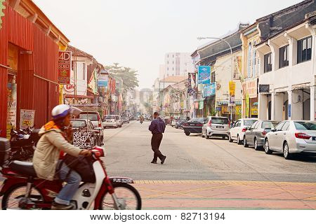 Malaysia, Penang, Georgetown - Circa Jul 2014: A Man Crosses A Typical Street In Georgetown As A Mot