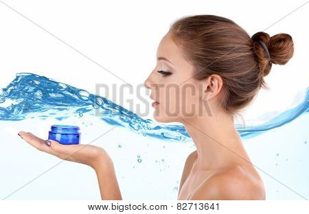 Beautiful young woman with cream on abstract blue water wave background