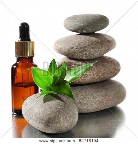 Spa stones with aromatic oils and green leaves isolated on white
