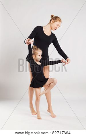 Woman teaching child to dance. mother and daughter gymnastics