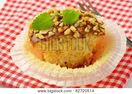 detail of chocolate muffin with chopped nuts on checkered dishtowel
