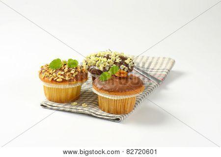 three chocolate muffins and fork on checkered dishtowel