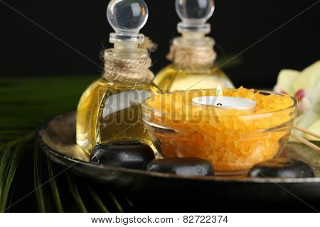 Beautiful spa composition with candle and orchid on dark background