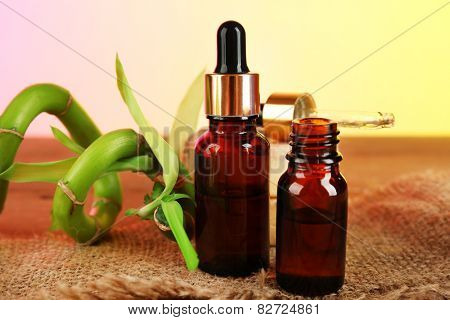Bottles with aromatic oils and bamboo on table on bright background
