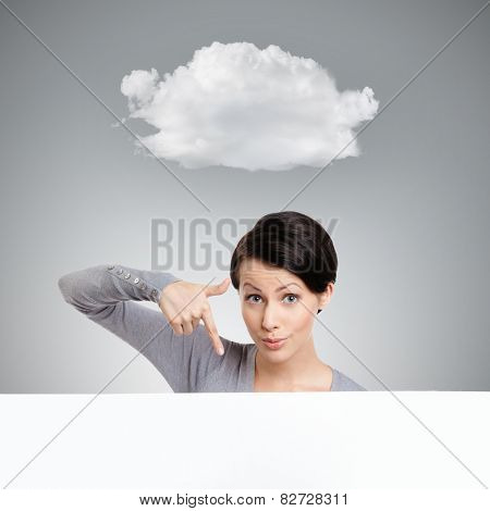 Young woman points down with finger , isolated on grey background