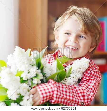 Adorable Little Toddler Boy With Blooming White Lilac Flower
