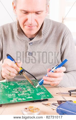 Serviceman soldering PCB with soldering iron in the service workshop