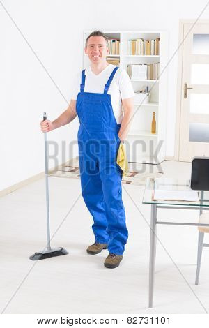 Smiling man cleaner standing with a broom at the office