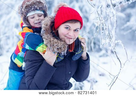 Portrait Of A Little Boy And His Mother In Winter Hat In Snow Forest