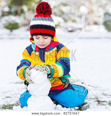 Lovely Little Boy In Colorful Clothes Making A Snowman