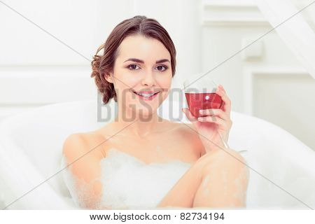 Beautiful young woman in bath with a wine glass