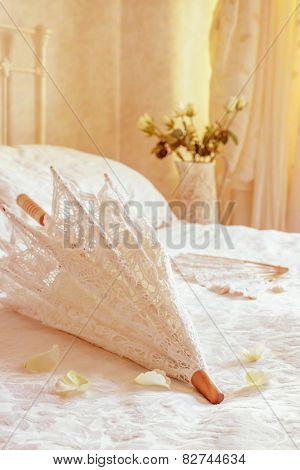 Lace parasol on the bed with wedding dress in the background