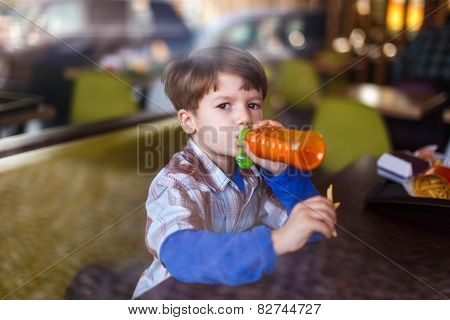 Little Boy In Fast Food Restaurant Drink Juice