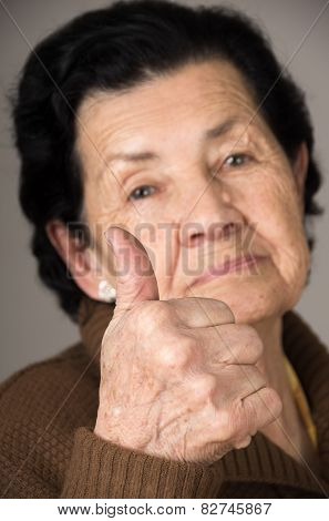 closeup portrait of grandma old woman holding thumb up