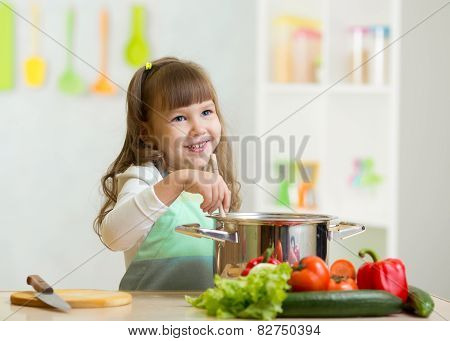 kid girl playing cook and makes a dinner