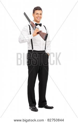 Full length portrait of an elegant guy holding a shotgun over his shoulder isolated on white background