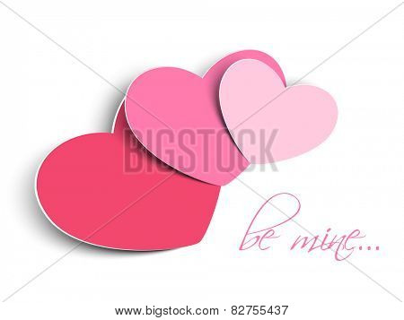 Pink glossy paper hearts with text Be Mine on white background for Happy Valentines Day celebration.
