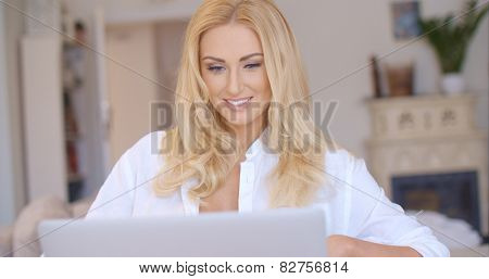 Close up Happy Young Blond Woman in White Shirt Using her Laptop Computer While at the Living Room.