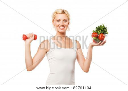 Weight loss concept - tanned woman lifting dumbbell and green salad isolated on white background