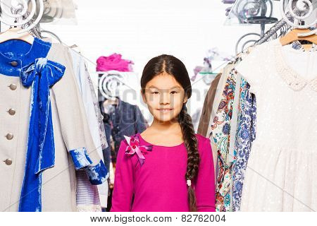 Small Asian girl with braid stands between clothes