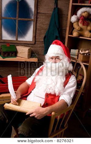 Santa Claus In Workshop With List