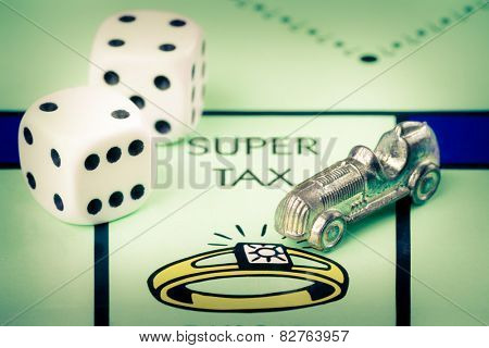 LONDON,UK - FEBRUARY 11, 2015 : Car token and dice next to the SUPER TAX space in a Monopoly game board