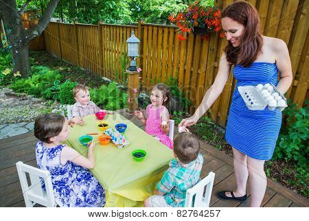 Mom Handing Out Easter Eggs To Paint To Her Children