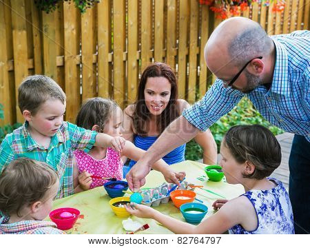 Father Helping Children Dyeing Their Easter Eggs