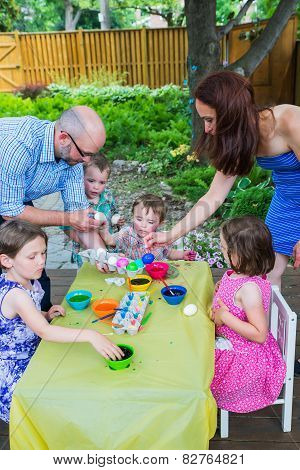 Family Painting And Dyeing Easter Eggs Together
