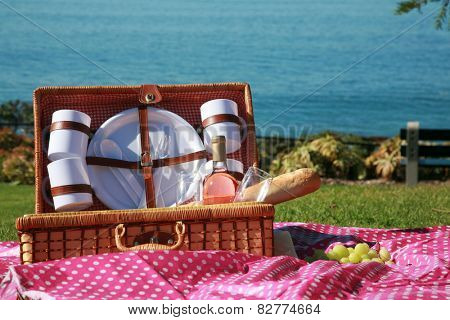 A Picnic at the beach with Wine, French Bread, Green Grapes, Mozzarella Cheese, Wine Glasses, Wicker Picnic Basket, Pink Pokka dot Cloth, Plates, Cups, Green Grass and the Blue Ocean.
