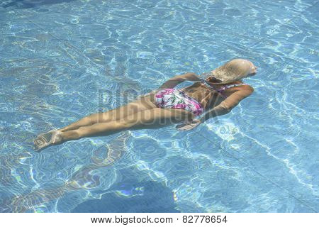 Aged Woman Swims Underwater In Bright Blue Water Of Pool.